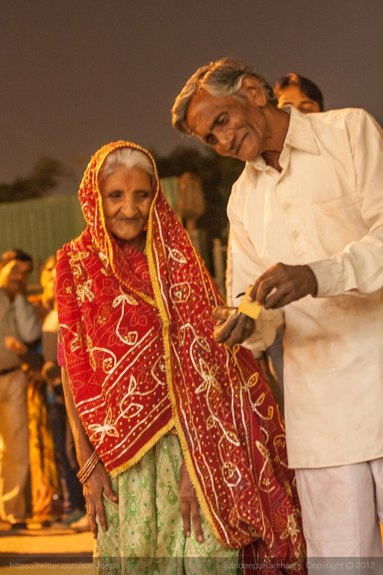 An old couple enjoying their Diwali  puja at the temple
