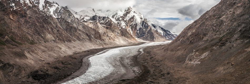 White snow of Drang Drung glacier flowing through the brown mountains of Greater Himalaya and Zanskar mountain ranges on Penzi la, the solitary mountain pass on the way from Kargil to Padum in Zanskar valley in India.