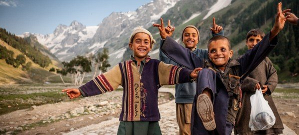 Four kids of the nomadic shepherd tribe called Gujjar from Kashmir doing an Indian dance called bhangra and singing with broad smiles on their faces in the beautiful landscape of Thajiwas glacier in Sonmarg.