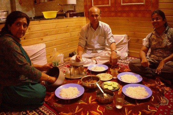 Lunch of chicken and rice in the carpeted living room with wooden flooring of a tourism officer's family in Srinagar.