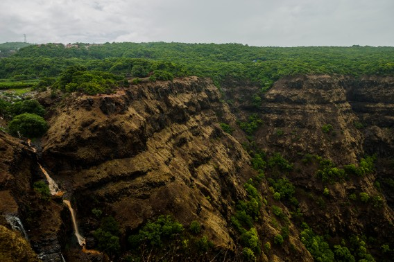Muddy and thin Chinaman waterfalls fall into a deep valley surrounded by a thick forest in Horses suddenly appear out of the thick mist that has fallen over the polo grounds in Mahabaleshwar, the most famous hill station in Maharashtra, India.