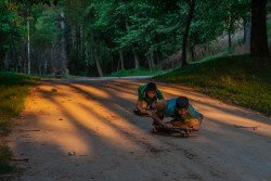 Two young boys from Pingwan in Jammu and Kashmir play with sledges made with a wooden plank and a metal rod made by them as they come sliding down a slope in the golden light in the evening as sunset.