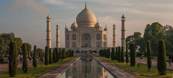 UNESCO certified heritage structure, India's iconic Taj Mahal in Agra symmetrical photo with the golden light at sunrise over the central dome of the Taj Mahal and its full reflection in the water canals